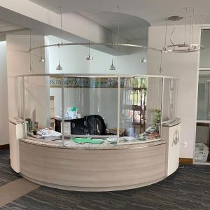 Curved Acrylic and Engineered Aluminum Safety Barrier for an Elegant Reception Desk